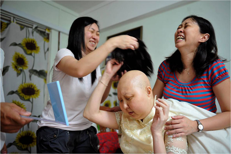 The mood in the Choa Chu Kang flat lightens up as Madam Foo Piao Lin's sisters get into the swing of dressing her up. The sisters, who do not wish to be named, help her don the cheongsam, adding a touch of light make-up and a wig in the style of a simple bob.
