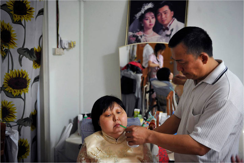 Madam Foo's husband, Mr Chin Yian Fook, 46, offering her a sip of juice amid the bustle of the preparations.
